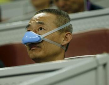 Homem usando máscara durante os jogos do Aberto de Pequim
